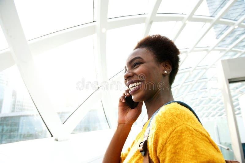 年轻非裔美国人的妇女谈话在手机在驻地 免版税库存图片