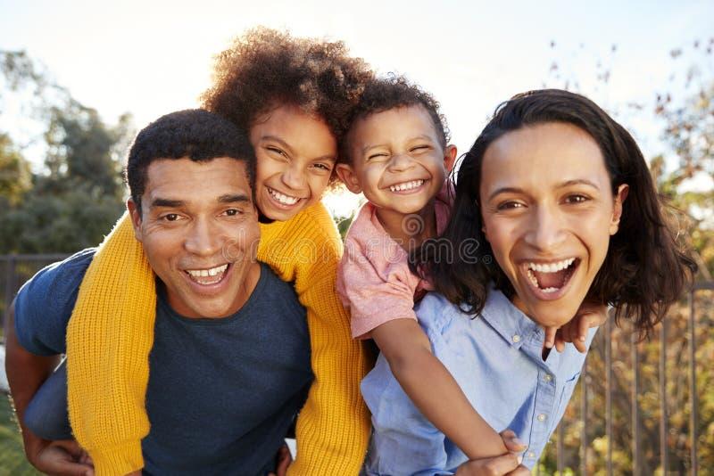 年轻非裔美国人的父母父母获得笑的乐趣扛在肩上他们的孩子在庭院,看对照相机和,clos 免版税库存照片