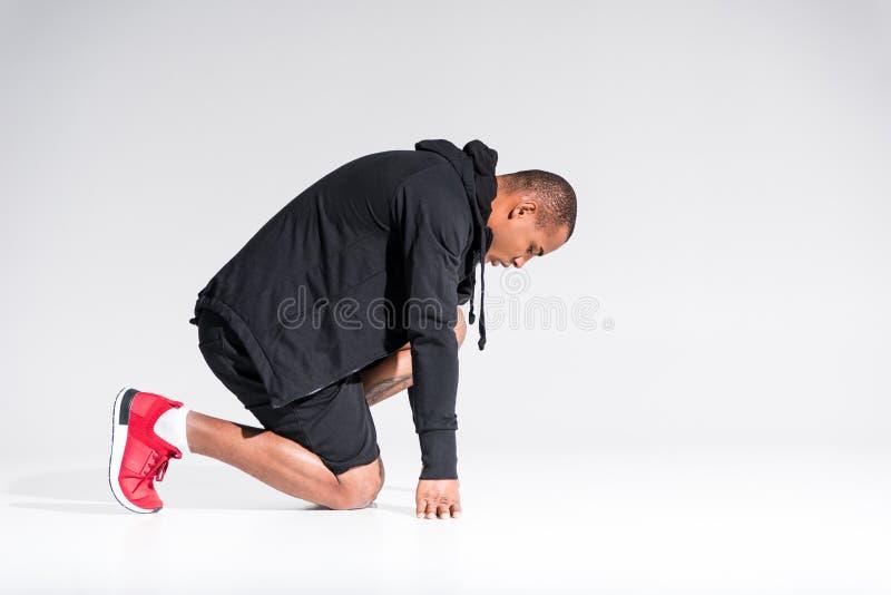 年轻非裔美国人的运动员侧视图有冠乌鸦下跪的 库存图片