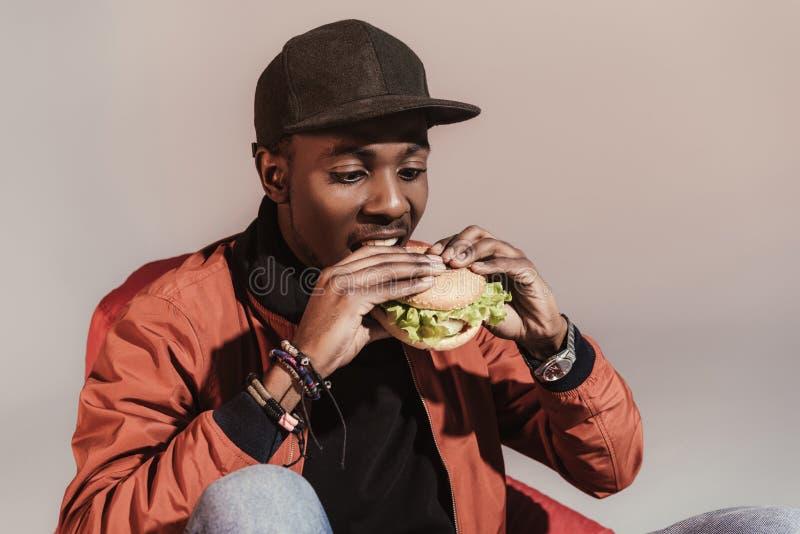 年轻非裔美国人的食人的汉堡包 库存照片