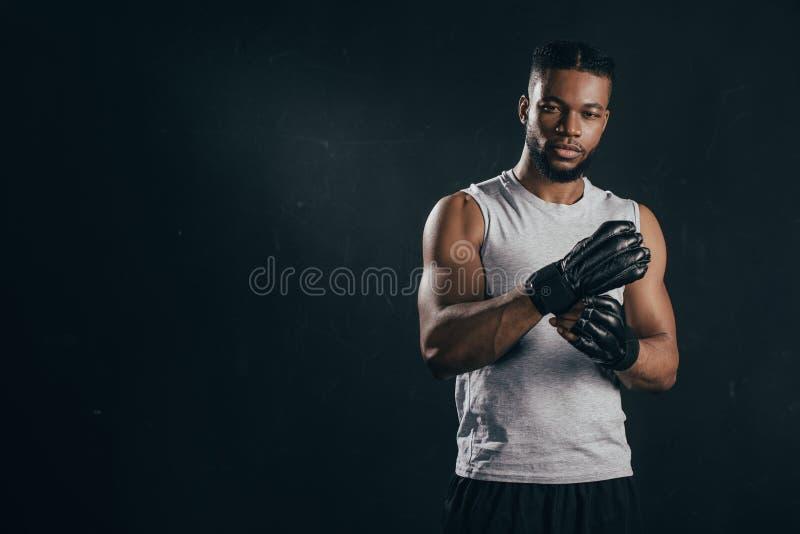 年轻非裔美国人的kickboxer佩带的手套和看照相机 库存图片