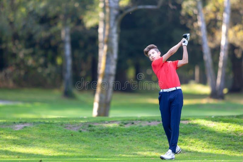 年轻高尔夫球运动员击中从在高尔夫球cour的发球区域射击的一个司机 库存图片