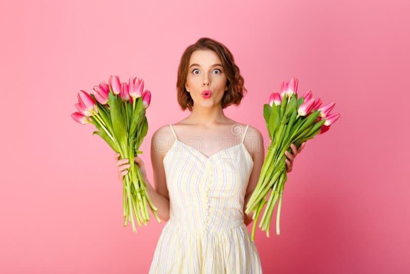 年轻鬼脸妇女画象有桃红色郁金香花束的  免版税库存照片
