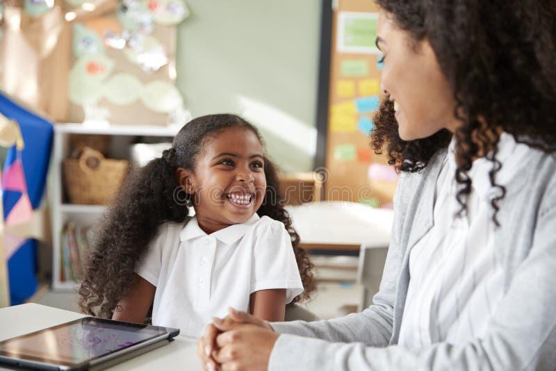 年轻黑人女小学生在与一台片剂计算机的一张桌上在学会一的一间幼儿学校教室坐一个用女性茶 免版税库存照片