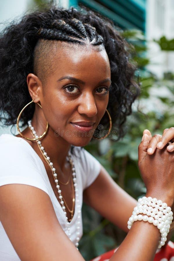 年轻黑人妇女坐户外看对照相机的,垂直 免版税库存图片