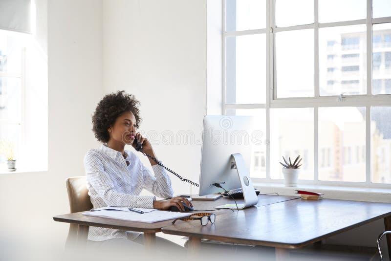 年轻黑人妇女谈话在电话在她的书桌在办公室 免版税图库摄影