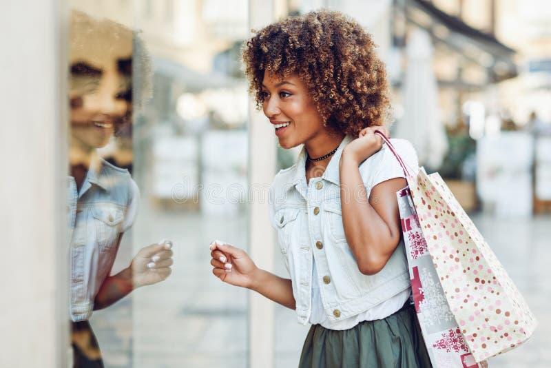 年轻黑人妇女,非洲的发型,看商店窗口 免版税库存照片