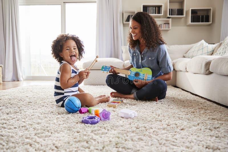 年轻黑人妈咪在家演奏有小孩女儿的尤克里里琴 图库摄影