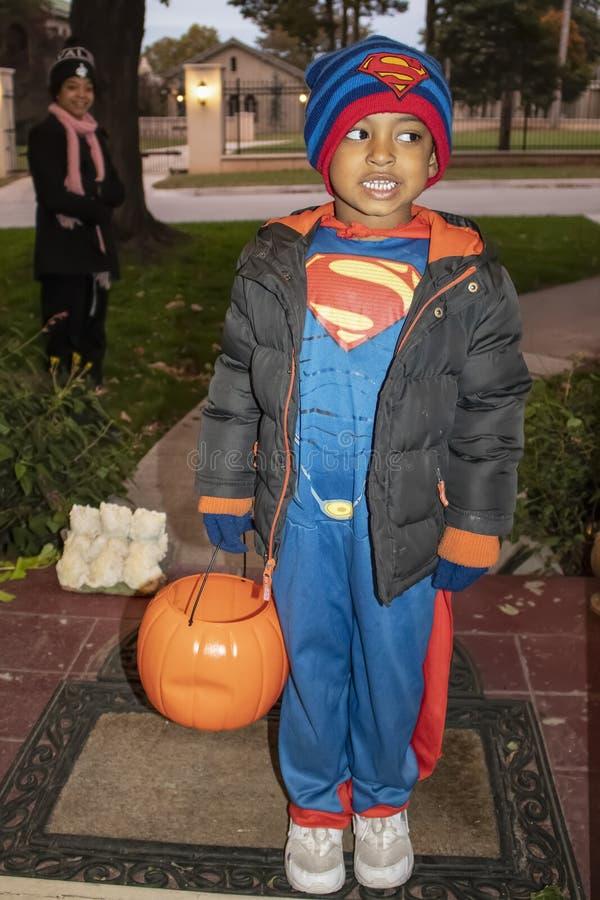 年轻黑人男孩在有南瓜糖果篮子的超人站立在门把戏r的服装和夹克穿戴了对待与母亲厕所 图库摄影