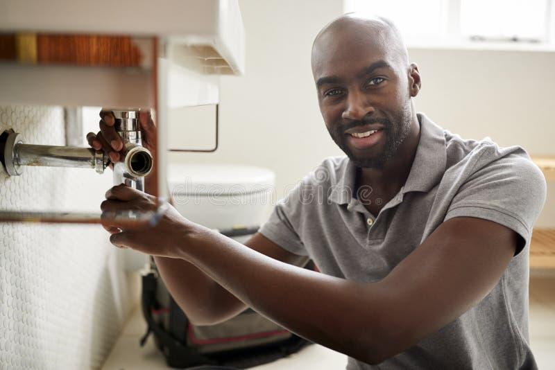 年轻黑人男性水管工坐修理卫生间水槽的地板,查寻对照相机,关闭 库存图片