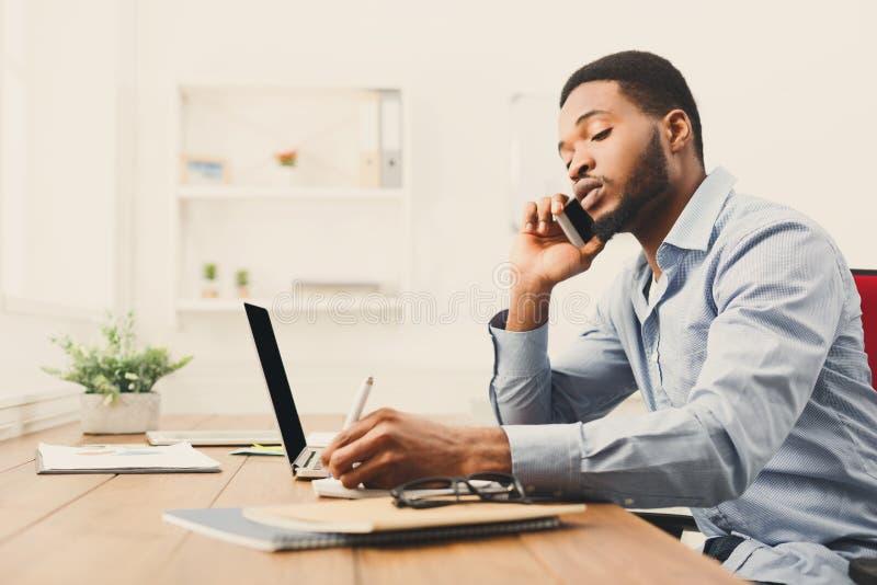 年轻黑商人谈话在手机 免版税库存照片