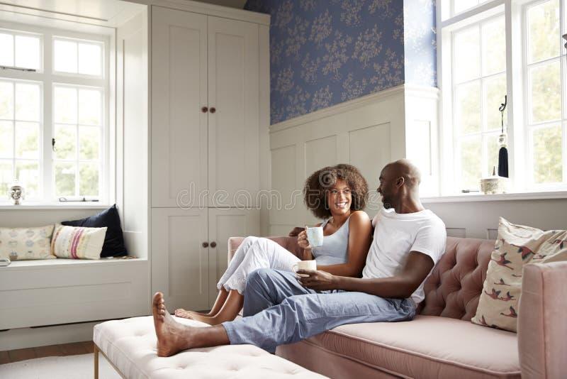 年轻黑夫妇一起坐在客厅饮用的咖啡的长沙发和谈话早晨,低角度,全长 库存照片