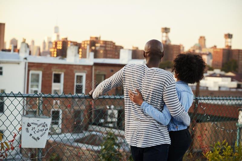 年轻黑夫妇拥抱在布鲁克林屋顶的,后面看法 免版税图库摄影
