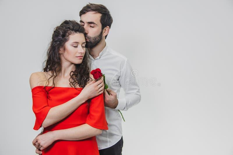 年轻,帅哥轻轻地盖他美丽的妻子 在这时间,一朵红色玫瑰 女孩在红色打扮 图库摄影