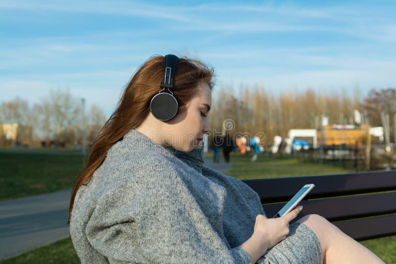 年轻,愉快的红头发人女孩在春天在河附近的公园听到音乐通过无线bluetooth耳机 免版税库存照片
