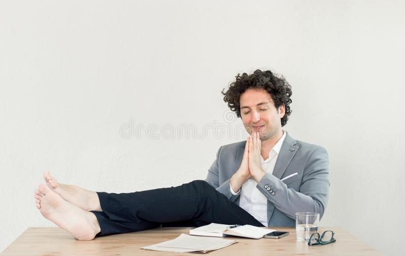 年轻,愉快,成功的白种人商人坐在有赤足书桌的办公室的和放松 免版税库存照片