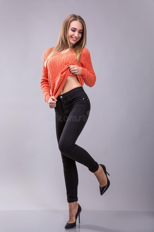 年轻,美丽,白肤金发的女孩画象在演播室 在一个灰色背景 库存图片