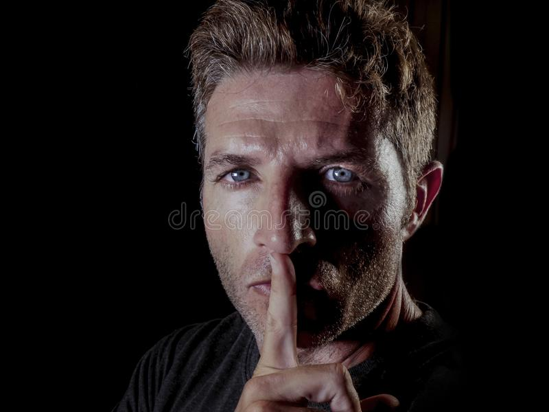 年轻30s人画象有手指的在他的在的沈默和威胁被关闭的手势的嘴唇警告或不讲话在polit 免版税库存图片