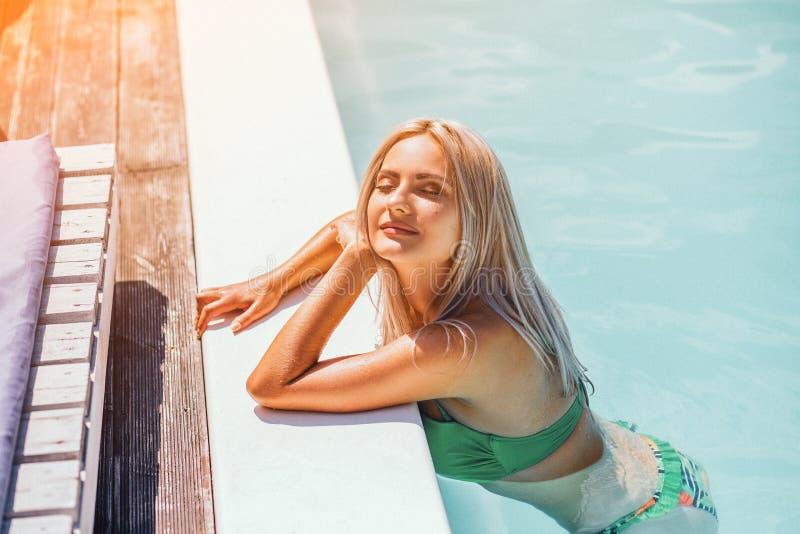 年轻Blondie妇女在游泳场晒日光浴 免版税库存照片