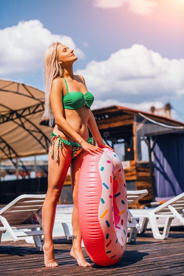 年轻Blondie妇女拿着一个可膨胀的游泳圆环,当站立在水池附近时 免版税图库摄影