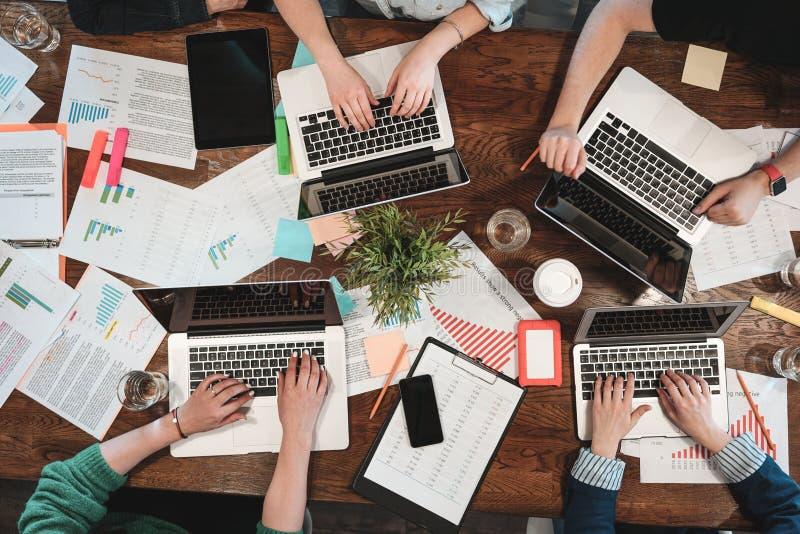 年轻coworking的人民顶视图研究膝上型计算机和纸张文件 小组使用膝上型计算机的大学生,当sittin时 免版税库存照片