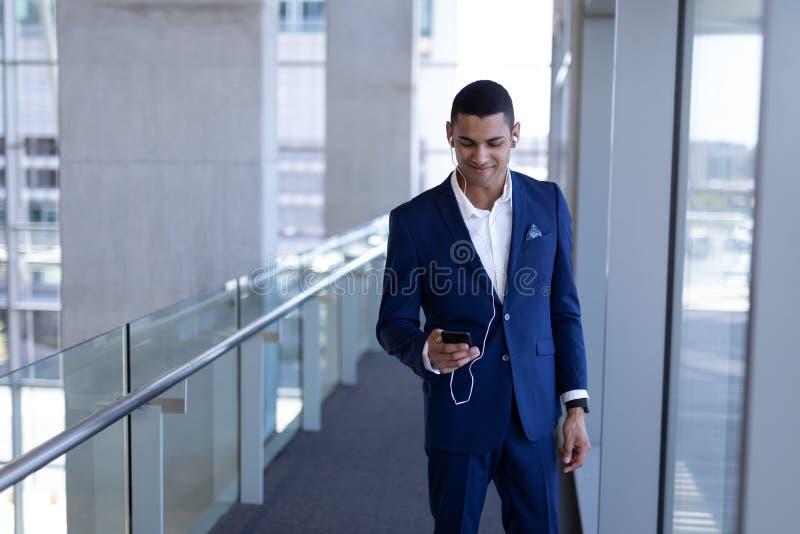 年轻mixed-race在手机的商人听的音乐在现代办公室 免版税库存图片