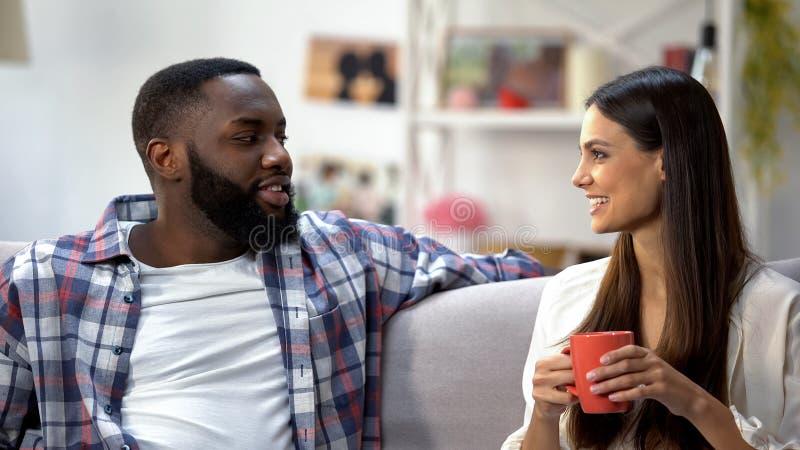 年轻mixed-race夫妇饮用的咖啡和在家谈话,好的交谈 库存照片