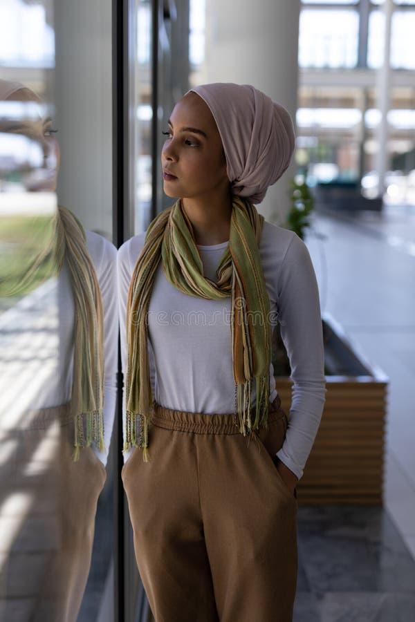 年轻mixed-race女性行政身分用在口袋的手在办公室 图库摄影