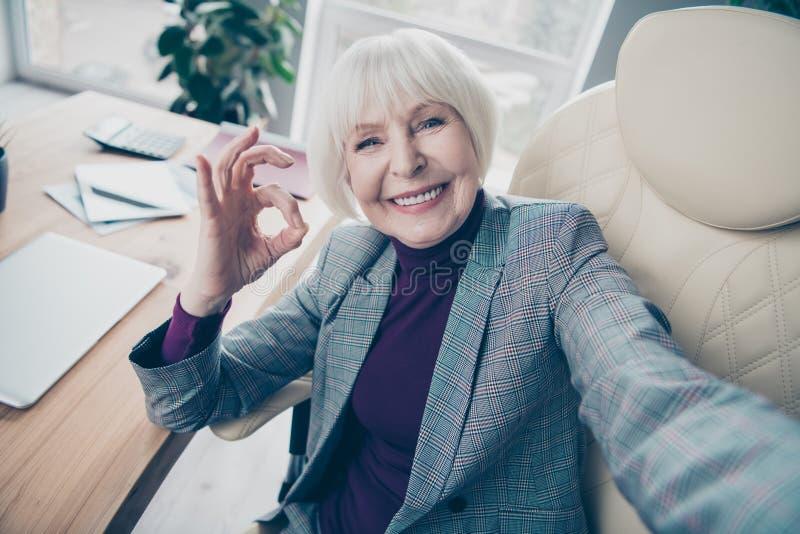 年迈的企业夫人休息日接近的照片做得到selfies okey标志了不起的工作坐办公室椅子穿戴格子花呢披肩服装 免版税库存照片