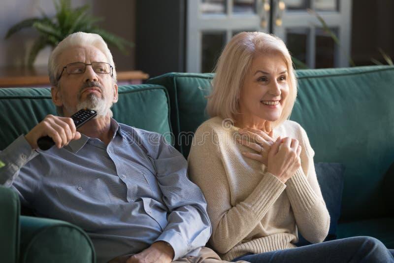 年迈的夫妇、妻子和丈夫看着电视展示,系列一起 库存图片