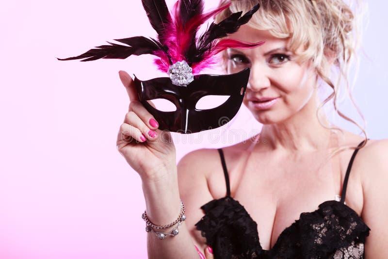 年迈的妇女中部拿着狂欢节面具 免版税库存照片