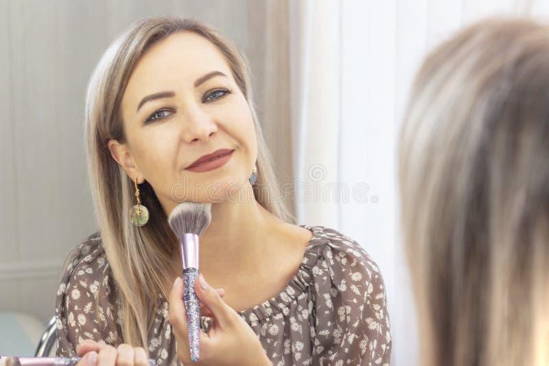 年迈的妇女投入她的构成 看在镜子 我自己应用在面孔的化妆师粉末与一把大刷子 免版税库存图片