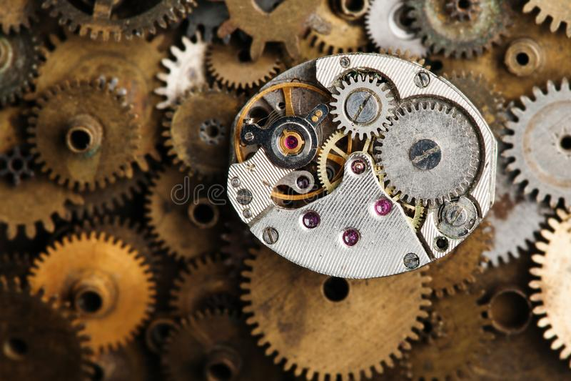 年迈的时钟机制宏指令视图 减速火箭的手观看在古铜齿轮背景的部分 库存图片