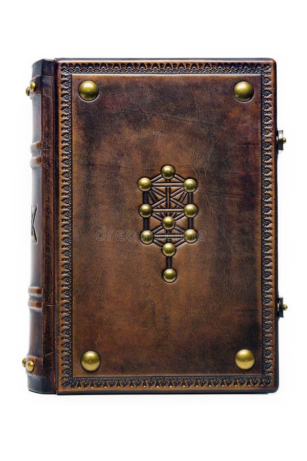 年迈的棕色皮革精装书与装饰了生物演化谱系图解标志 免版税库存照片