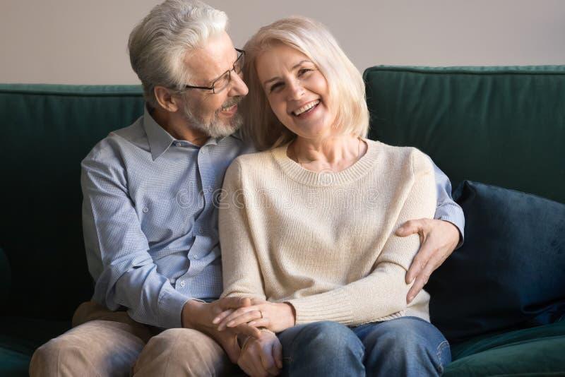 年迈的爱恋的丈夫拥抱的微笑的妻子顶头射击画象  免版税库存图片