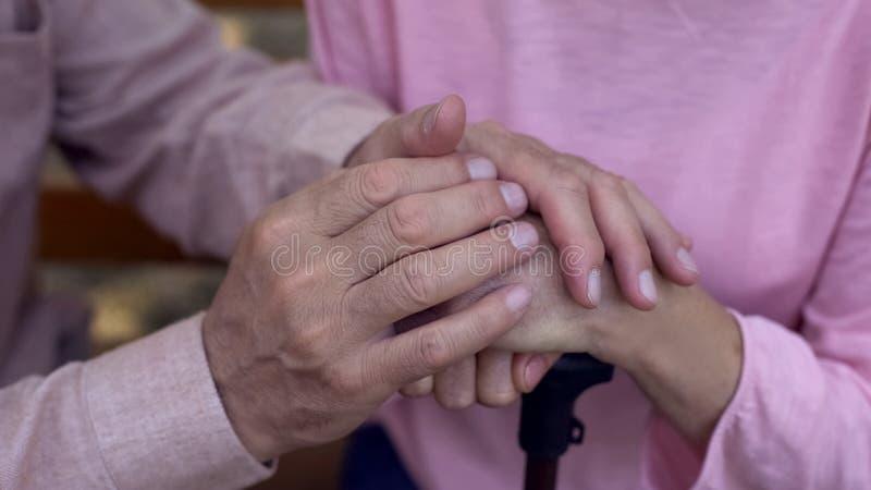 年迈的男性覆盖物女性手,疗养院护理,家庭支持,协助 免版税库存图片
