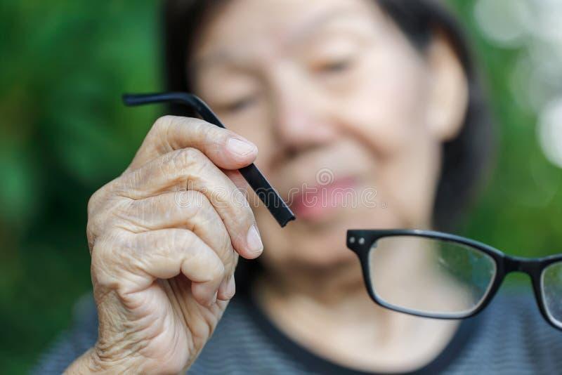 年长亚洲妇女修理打破的玻璃 库存图片
