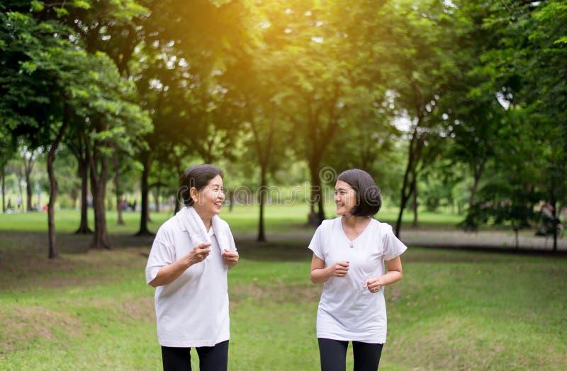 年长亚裔妇女画象有跑在公园的女儿的在清早一起,健康和小心概念 图库摄影