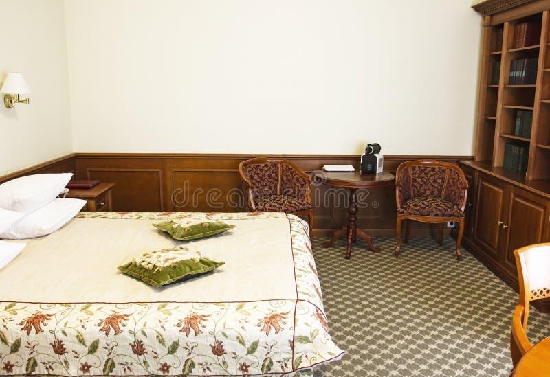 年长人卧室有书橱的,古色古香的桌,减速火箭的内部 免版税库存图片
