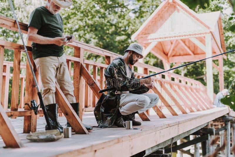 年长人和他的儿子身分在木桥 图库摄影
