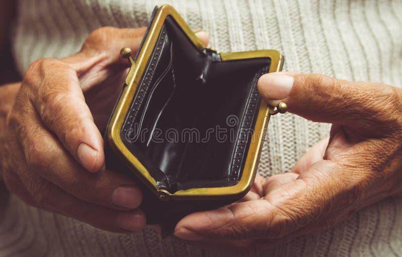 年长人在他的手上拿着一个空的钱包 葡萄酒空的pu 库存照片