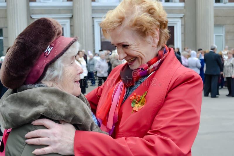 年长人在俄罗斯,在街道上的两个熟悉的亚裔女子的天 免版税库存照片