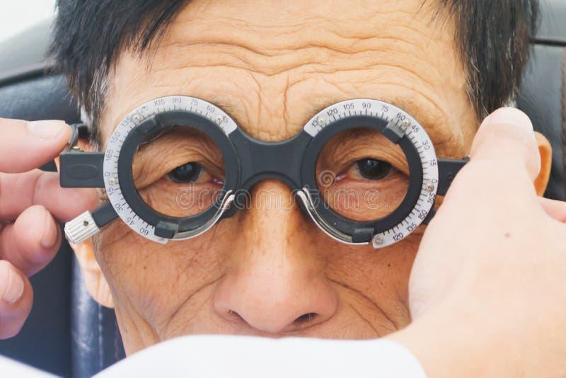年长人安排hes眼睛审查由一个测试工具的一个眼科医生在现代诊所, 库存图片