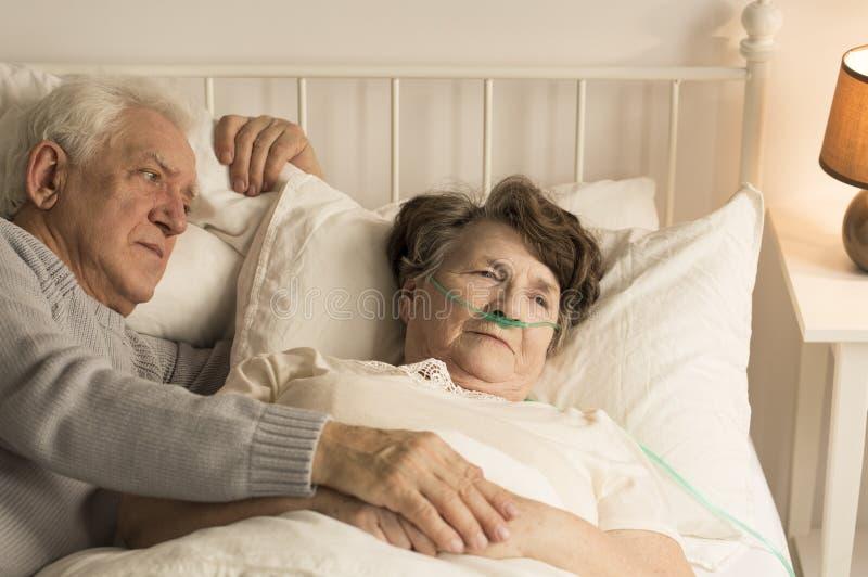 年长人支持的死的妻子 库存图片