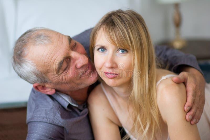 年长人是拥抱和亲吻他的在床上的性感的女用贴身内衣裤的年轻妻子在他们的家 加上年龄 免版税图库摄影