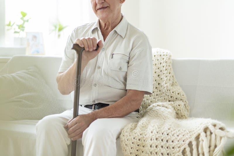 年长人特写镜头用拐棍在护理房子里 库存图片