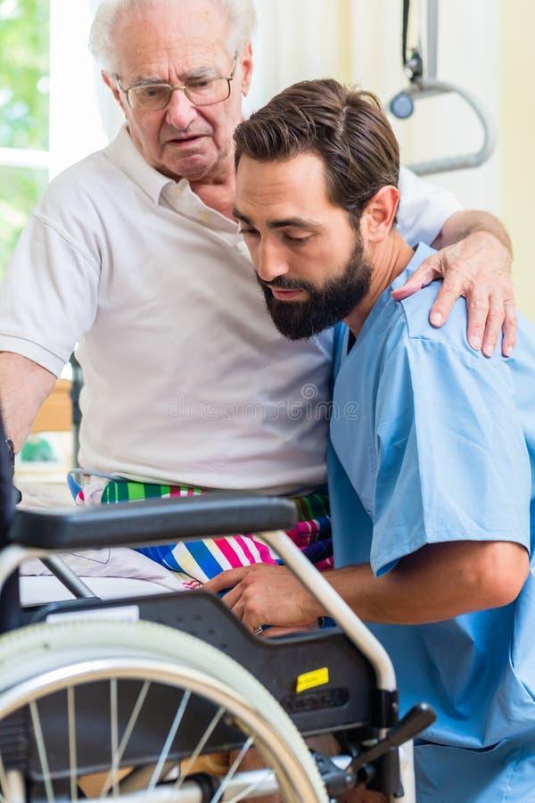 年长关心护士帮助的前辈从床到轮椅 免版税库存图片