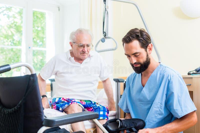 年长关心护士帮助的前辈从床到轮椅 免版税库存照片