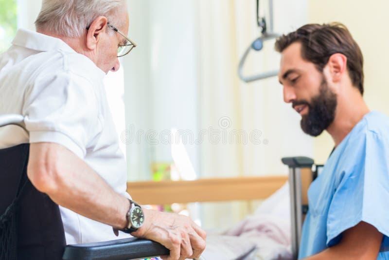 年长关心护士帮助的前辈从床到轮椅 免版税图库摄影
