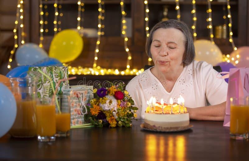 年长在她的生日庆祝的妇女吹的蜡烛 免版税库存照片